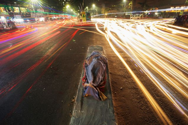 Osman Gani, 28. He does work of loading commodities in different shops of Chattogram city all day long. In night, he falls asleep on the road divider in Kazir Dewry area of the city. The photo was taken on January 30, 2018
